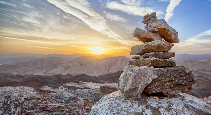 A rock cairn in the mountains at sunset.