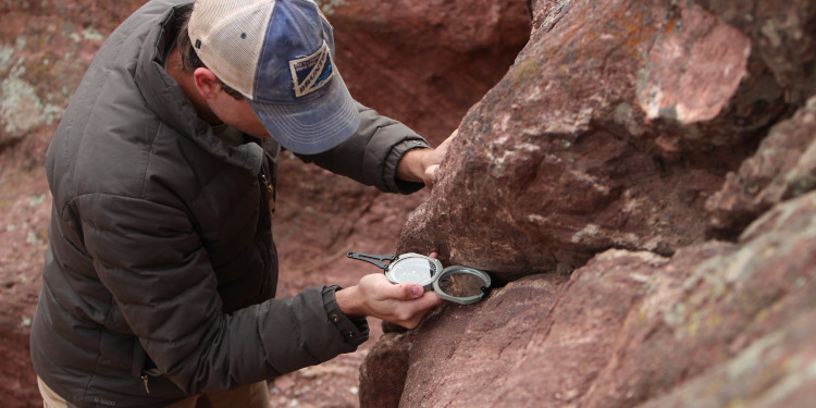 A man uses a Brunton Transit compass to take field measurements.