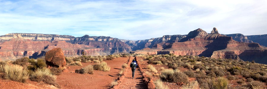 A person hikes on a red desert trail with soaring canyon walls in the distance.