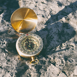 A brass compass sits open on a rocky surface.