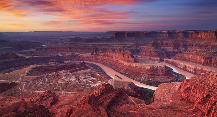 Sunset over a desert canyon with a horseshoe bend and a river flowing through it.