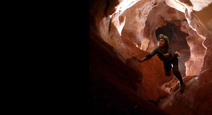 A woman moves through a cave wearing protective equipment.