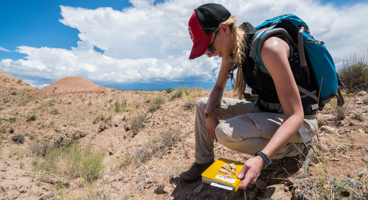 A young woman kneels in an arid environment with a notebook and field tools.