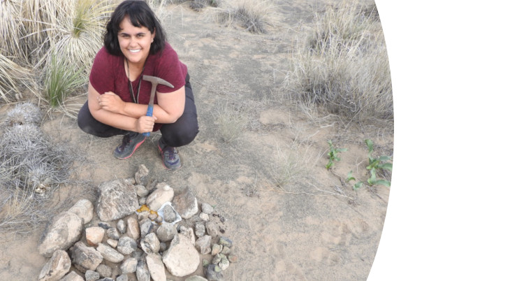 A woman holding a rock hammer squats near a pile of rock samples in arid terrain.
