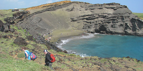 People walk on a grassy hillside with a dark sandy outcrop and a beach in the background.