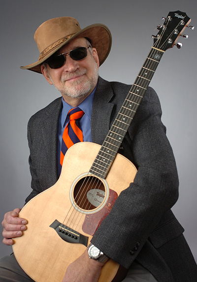 GSA President Donald Siegel holding an acoustic guitar and wearing an outback hat.