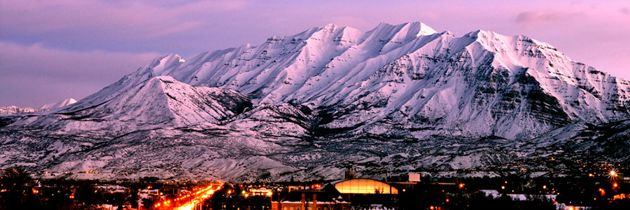A snow-caked Mount Timpanogos bathed in purple alpenglow.
