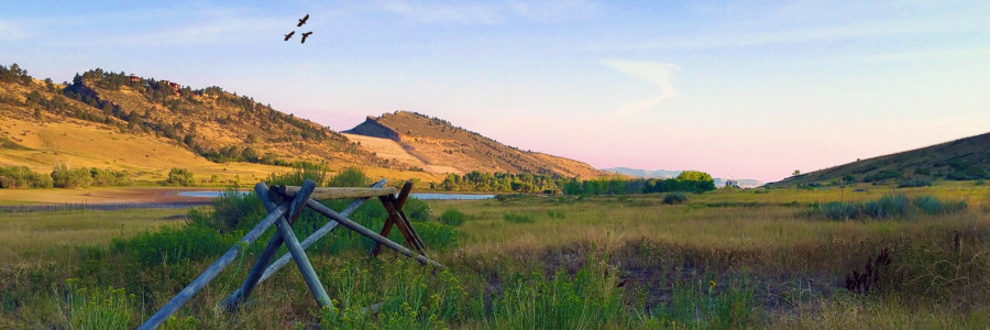 A buck and rail fence fills the foreground of a lush, green valley with layered rock formations in the background.