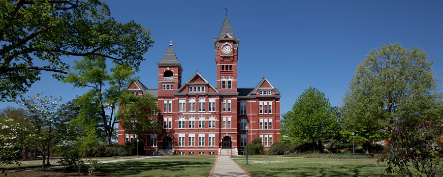 A stately red brick building rises from a well-manicured lawn crisscrossed by sidewalks.
