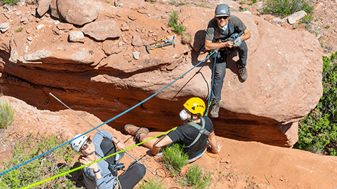 Three people wear climbing gear near a large crack in red sandy stone.
